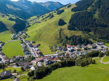 Aerial View Of Hinterglemm Village And Mountains With Skiing Lifts In Saalbach-Hinterglemm Skiing Region In Austria On A Beautiful Summer Day.