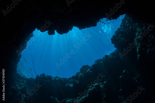 Sunlight filters into a dark, underwater cave in the Republic of Palau Fototapet