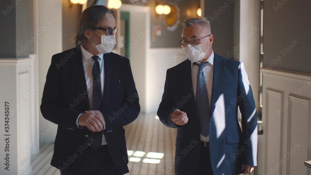 Fototapeta Senior business partners in masks discussing deal walking in business center hall
