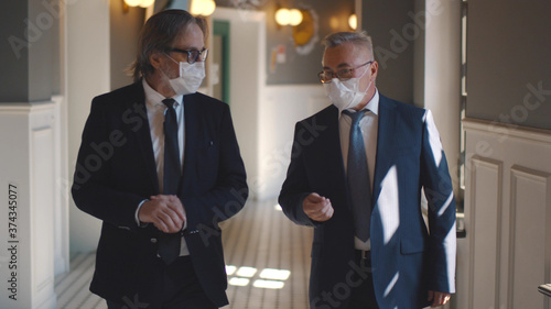 Obraz Senior business partners in masks discussing deal walking in business center hall - fototapety do salonu