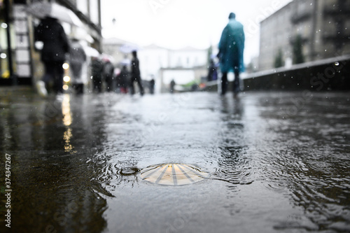 Fototapeta Bronze scallop as a waymark in the old town of Santiago de Compostela on wet ground during rain with pilgrims in ponchos in the background