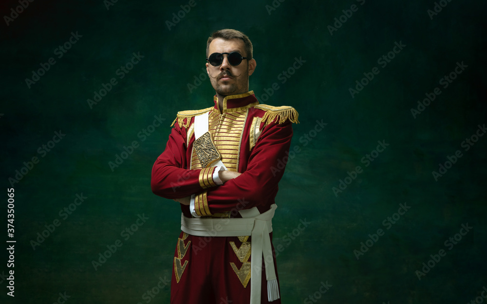 Fototapeta Wearing stylish eyewear. Young man in suit as Nicholas II isolated on dark green background. Retro style, comparison of eras concept. Beautiful male model like historical character, monarch, old