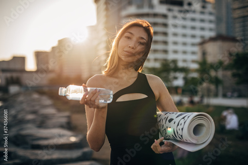 Obraz na plátně Beautiful Chinese woman drinking water after yoga practice outdoors in the city