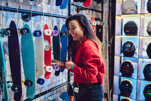 Fotografie, Obraz Cheerful Japanese hipster girl in trendy clothing laughing near rack in store sp