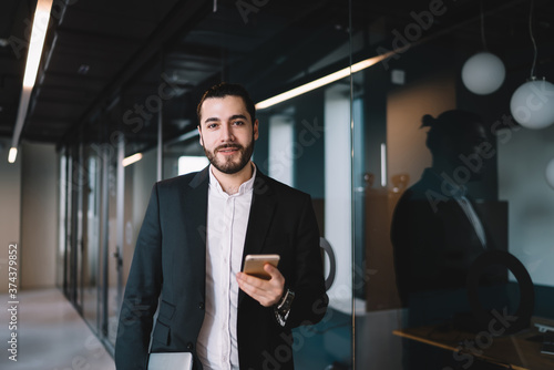 Cuadros en Lienzo Businessman standing with smartphone in hand