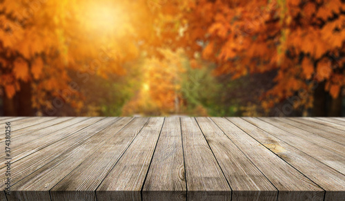 Wooden desk on autumn blur abstract natural background Fotobehang