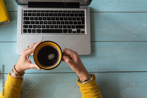 Foto Woman studying from home holds a cup of coffee
