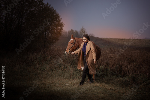 Obraz na plátně Young brunette woman in a beige coat posing with a red brown horse