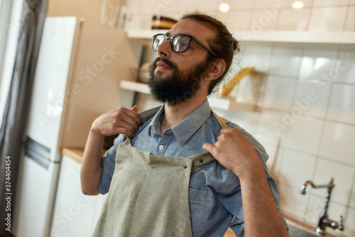 Tablou Canvas Young man, professional cook in glasses putting on his apron while getting ready to prepare a meal, standing in the kitchen
