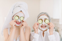 Spa And Wellness. Anti Age Mask. Skin Care For All Ages. Ssmiling Attractive Senior Gray Haired Woman With Her Granddaughter Making Clay Facial Masks And Covering Eyes With Cucumber Slices