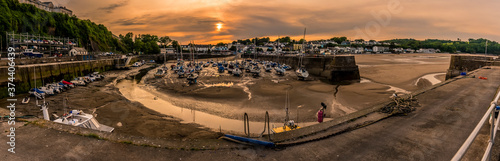 Fotografia The sun sets over pleasure craft in Saundersfoot  harbour, Wales at low tide in