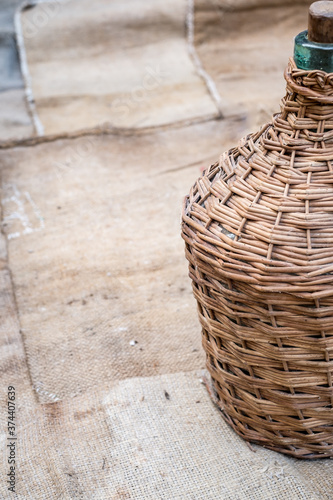 Fotografia demijohn and old wood wine barrel on jute sack