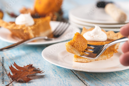 Obraz na plátne Closeup perspective shot of a bite of pumpkin pie on a fork with plates and slices of pumpkin pie blurred in the background on a rustic blue painted wood table surface