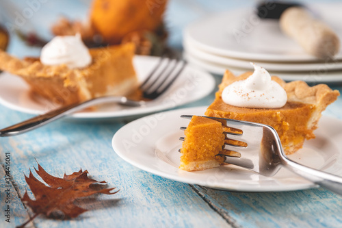 Leinwand Poster Closeup perspective shot of a slice of pumpkin pie with a fork cutting into it with plates and pie blurred into the background on a rustic blue painted wood table surface