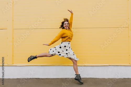 Fotografía Full-length portrait of excited trendy woman running on yellow background