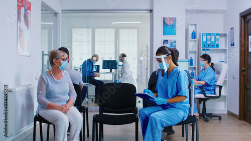 Nurse and senior patient going in hospital examination room from waiting area Wallpaper Mural