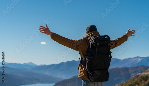 Cuadros en Lienzo A traveler with a backpack stands on the top of the mountain and holds his hands