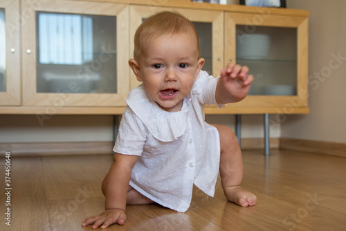 A cute little boy crawling around the house Happy baby crawling on the floor towards the camera Wallpaper Mural