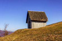 Small Wooden House On A Hillside In Autumn