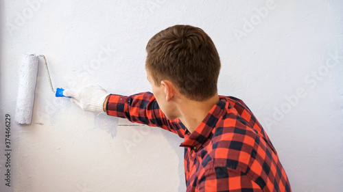 guy in red checkered shirt paints wall in light grey color making repair on mode Wallpaper Mural