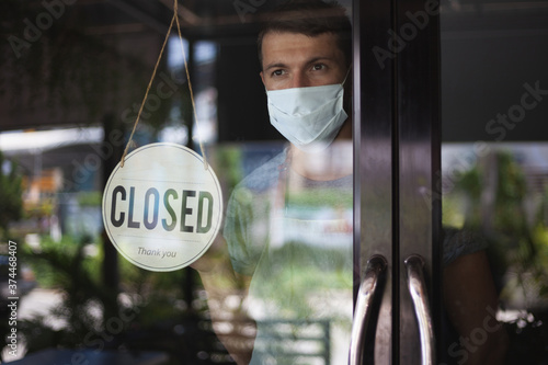 Chef in safety mask hanging up sign closed on restaurant door. Fototapete