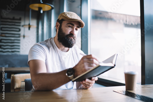 Obraz na plátně Serious bearded mature man in hat sitting in cafe interior writing in notepad du