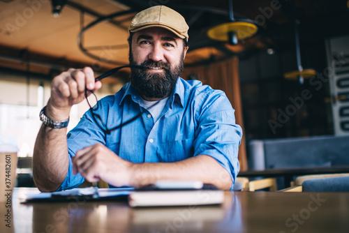 Half length portrait of smiling caucasian male in trendy casual wear and hat enj Billede på lærred