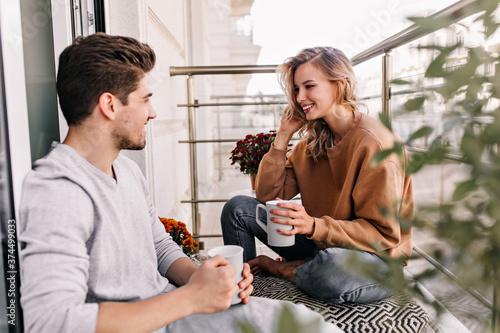 Cheerful lady talking with husband at balcony Fotobehang