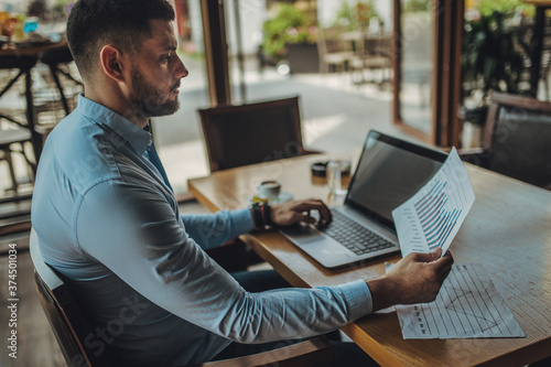 Foto A businessman is working on a laptop in a restaurant, looking at chart on paper