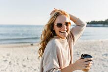 Winsome Woman In Sunglasses Spending Cold Morning Beside Sea. Blithesome Blonde Lady With Cup Of Coffee Laughing At Ocean Coast