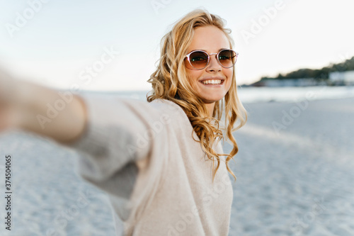 Fototapeta Cute woman with wavy blond hair sincerely smiles and takes selfie at sea