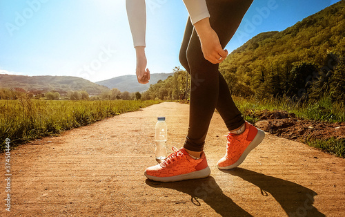 Fotografie, Obraz Female person in sportswear bending over to pick water bottle, after training