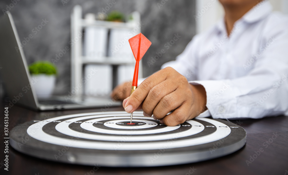 Fototapeta Close up hand of business man holding dart on target with financial graph paper with laptop on table, successful achievement, success and win concept