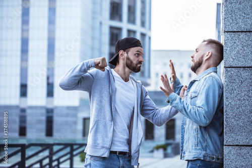 Vászonkép Two adult bearded men are fighting in the street