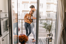 Man Embracing Wife At Balcony. Relaxed Couple Drinking Coffee In Weekend.