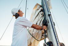 Mature Captain Looking Up While Adjusting Sail. Senior Yachtsman Preparing A Boat For A Vacation Trip.