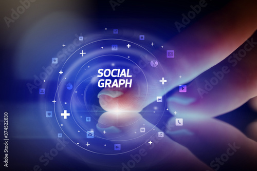 Fotografia Finger touching tablet with social media icons and SOCIAL GRAPH