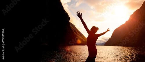 Papel de parede Silhouette einer Frau mit ausgebreiteten Armen bei Sonnenaufgang  an einem See