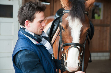 Portrait of a jockey standing by horse in stable