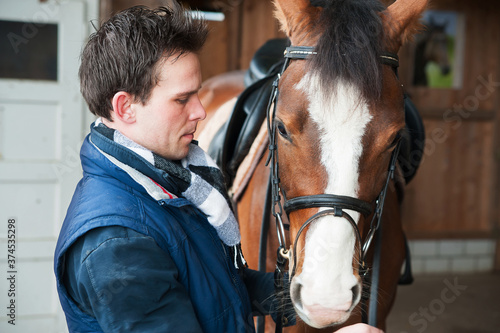 Photo Portrait of a jockey standing by horse in stable
