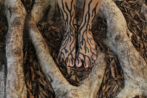 Tablou Canvas Feet with painted roots surrounded by roots in a park