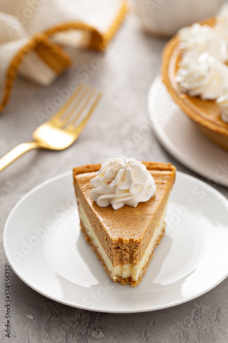 Obraz na plátně Slice of pumpkin pie with a cheesecake layer topped with whipped cream with a bi