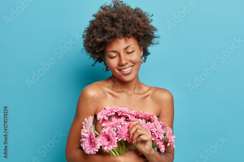 Beautiful tender woman stands with closed eyes, naked body, carries pink gerbera Canvas Print