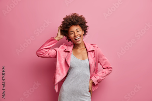 Photo Amused carefree young Afro American woman with closed eyes, enjoys awesome day off, dressed in stylish clothes, smiles broadly, isolated on pink background, feels lucky, free and successful