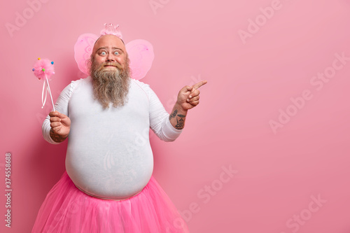 Funny man wears fairy costume, invites you on holiday or costume party, indicates right at blank space, holds magic wand, poses against rosy wall Poster Mural XXL