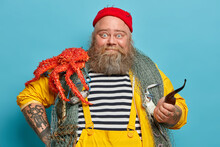 Photo Of Bearded Experienced Sailor Poses With Fishing Net, Big Red Crab On Shoulders, Smoke Pipe, Welcomes On Board, Enjoys Marine Cruise During Summer Vacation. Bearded Captain Has Sea Life