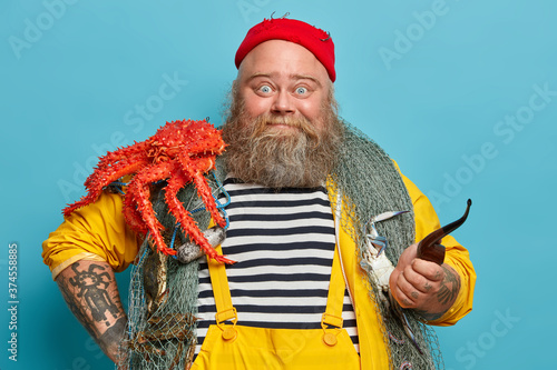 Fototapeta Photo of bearded experienced sailor poses with fishing net, big red crab on shoulders, smoke pipe, welcomes on board, enjoys marine cruise during summer vacation