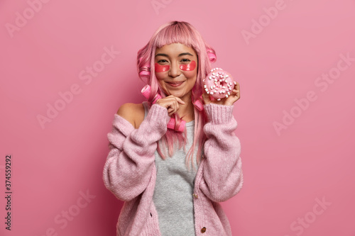 Horizontal shot of satisfied young Asian woman enjoys beauty skin treatments and Slika na platnu