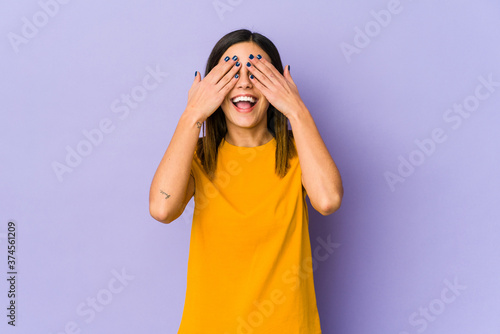 Photo Young woman isolated on purple background covers eyes with hands, smiles broadly waiting for a surprise