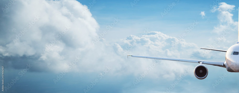 Fototapeta Commercial airplane jetliner flying above dramatic clouds in beautiful light. Travel concept.